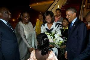 The Obamas are welcomed to Senegal by President Macky Sall and First Lady Marème Sall, June 26,2013. Apparently, to be most presentable, the hair of the flower-bearing girl was styled to look contemporary and Western, and not reflect the unique, skillful artistry of the country's own cultural traditions, as does the women's ceremonial dress. White House Photo: Pete Souza.