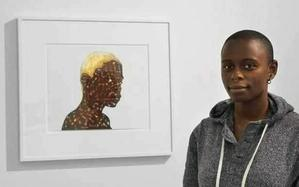 Artist Toyin Odutola with her work.  Photo courtesy: Jack Shainman Gallery
