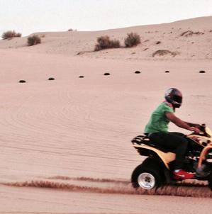 Duplessis zipping across a desert in Dubai. He was invited to speak there by a Middle East society of news designers