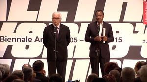 Paolo Baratta and Okwui Enwezor at awards program. Biennale video screen shot