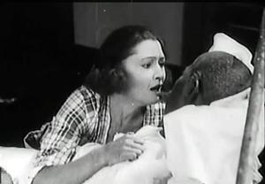Eve Mason (Iris Hall) at her grandfather's deathbed in Symbol of the Unconquered (1920)