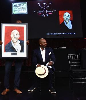 Dave Chappelle is presented with portrait created by Art For Life participant