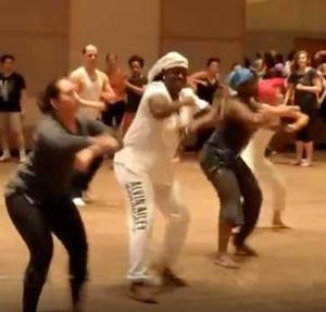 "Danys ""La Mora"" Pérez (in white attire) leads an Afro-Cuban dance master class in Minneapolis. Photo: You Tube"