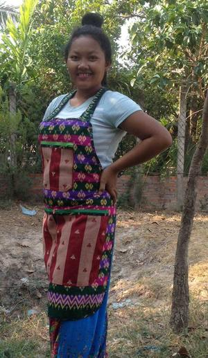 Ren, a survivor, program graduate and Musasama's translator. She is wearing an apron she made.