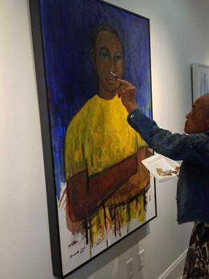 Samella Lewis touching up painting at Stella Jones Gallery, 2016